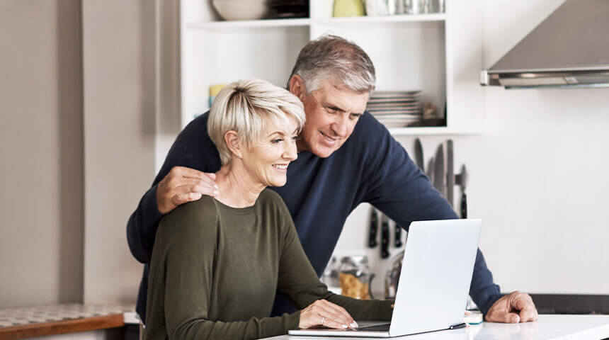Couple looking at laptop in kitchen